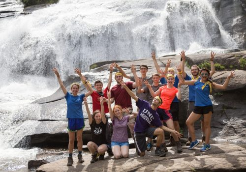 happy group in front of waterfall